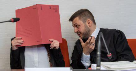 Die Angeklagte Jennifer W. hält im Gerichtssaal einen roten Aktendeckel vor das Gesicht. Rechts neben ihr sitzt Anwalt Ali Aydin.