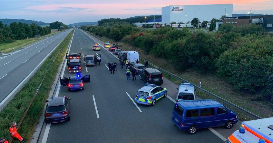 Polizisten und Helfer stehen mit ihren Fahrzeugen auf der Autobahn 9.