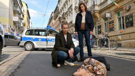 """""""Tatort: Unsichtbar"""": Anna Schneider (Milena Tscharntke) ist auf offener Straße tot zusammengebrochen, die Ermittlerinnen Leo Winkler (Cornelia Gröschel, l.) und Karin Gorniak (Karin Hanczewski) sehen sich die Tote an. (ili/spot)"""