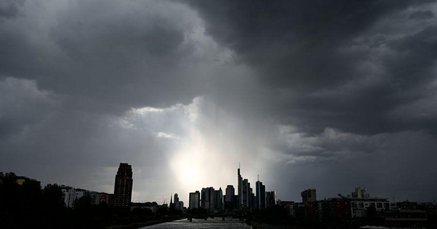 Dunkle Wolken ziehen über die Bankentürme und Hochhäuser während der Regen über der Bankenstadt einsetzt. (Archivbild)