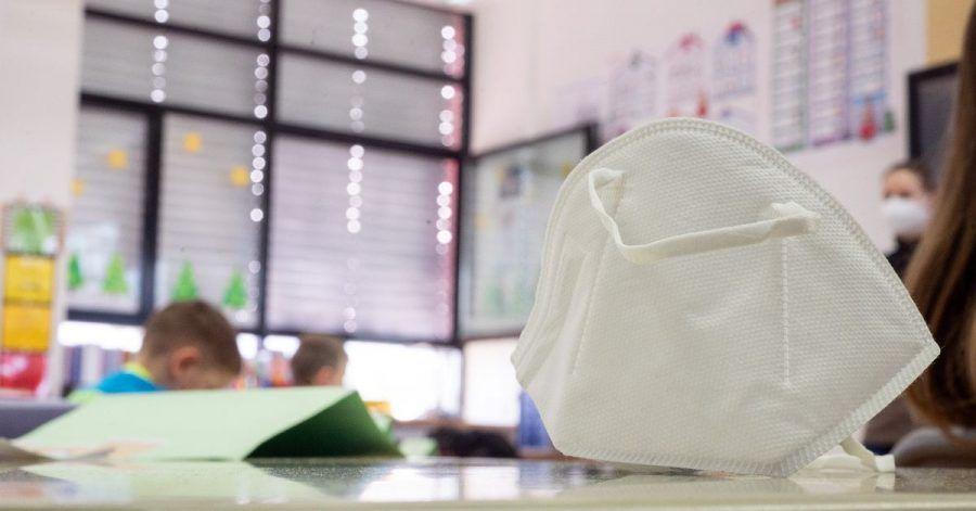 Eine FFP2-Maske liegt in einer ersten Klasse an einer Grundschule.