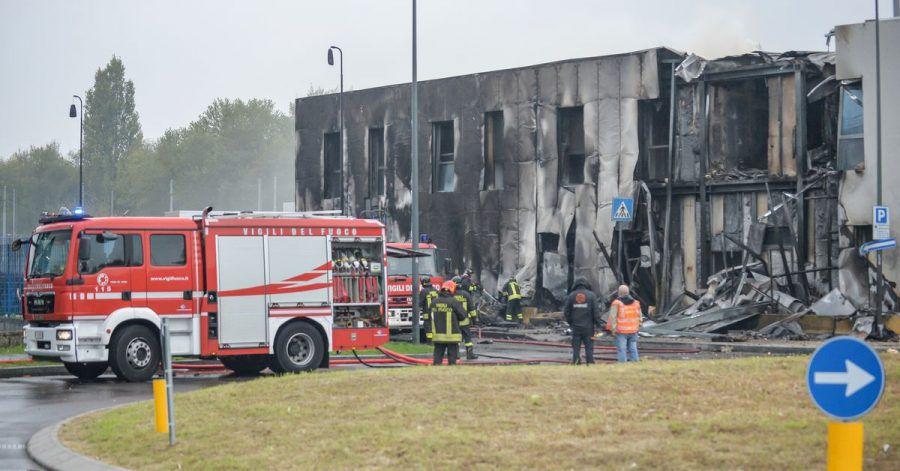Feuerwehrleute stehen an der Unfallstelle, nachdem ein Leichtflugzeug kurz nach dem Start abgestützt und in ein leerstehendes Bürogebäude gekracht ist.