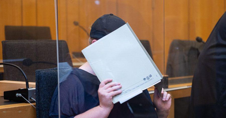 Zu Beginn des Prozesses im Missbrauchskomplex Münster sitzt die Mutter eines Opfers im Landgericht Münster und verdeckt ihr Gesicht mit einer Mappe. (Archivbild)