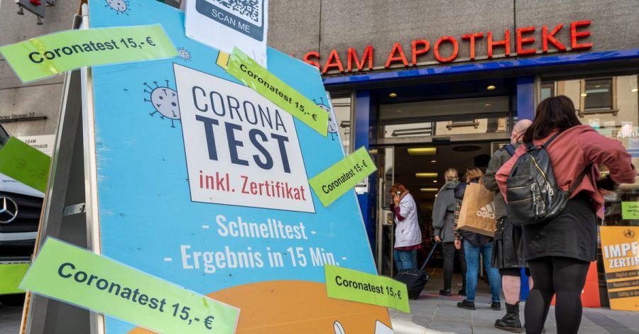 Passanten stehen in der Münchner Innenstadt vor einer Apotheke, die Coronatest für 15 Euro anbietet.