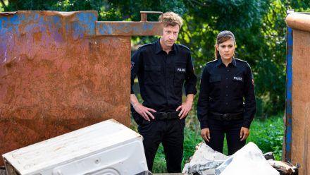 """""""Friesland - Bis aufs Blut"""": Henk Cassens (Maxim Mehmet) und Süher Özlügül (Sophie Dal) sind bestürzt als sie sehen, wer da tot im Container liegt. (cg/spot)"""