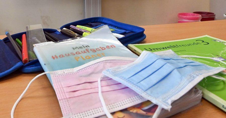 Masken liegen während einer Pause auf Arbeitsmaterialien eines Schülers in einem Klassenraum einer Grundschule.