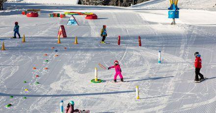Im Kinderland Hüttenberg imSchweizer Ferienort Braunwald können sich die Kleinsten ans Skifahren herantasten.