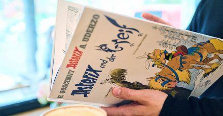 """Ein Mann schaut in den neuen Asterix-Band """"Asterix und der Greif""""."""