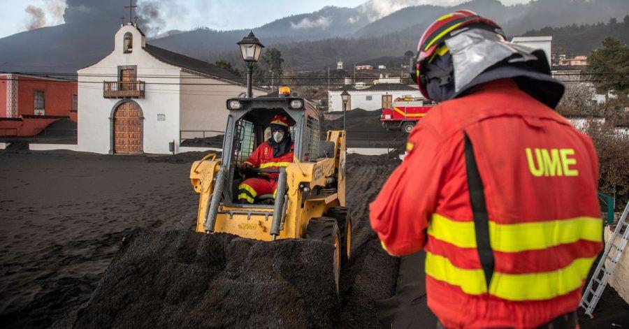 Einsatzkräfte des Militärs entfernen schwarze Asche vom Vulkan, der hinter der kleinen Kirche auf der Kanareninsel La Palma weiter Lava ausstößt.