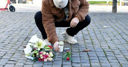Ein Mann legt am Tatort Blumen und eine Kerze für den Musiker Einár nieder.